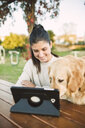Smiling young woman using a tablet in a park with her dog - RAEF02258