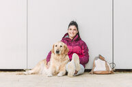 Portrait of a smiling young woman with her Golden retriever dog sitting at a wall - RAEF02261