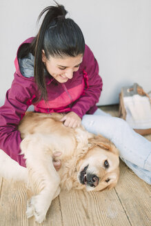 Happy young woman stroking and playing with her golden retriever dog - RAEF02264