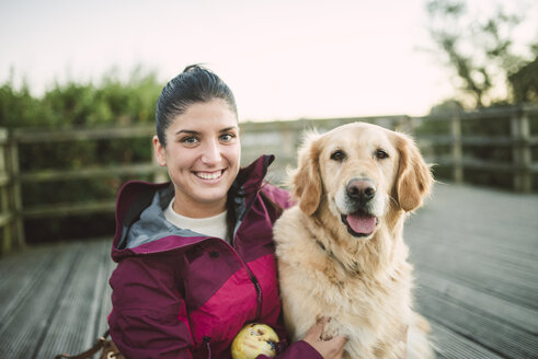 Portrait of a happy young woman with her Golden retriever dog outdoors - RAEF02267