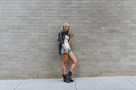 Portrait of young woman with cell phone at brick wall - BOYF01123
