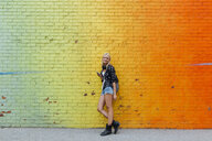 Portrait of young woman with cell phone at colorful brick wall - BOYF01135