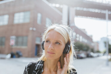 USA, New York City, Brooklyn, portrait of young woman listening to music with headphones in the city - BOYF01144