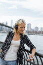 USA, New York City, Brooklyn, smiling young woman standing at the waterfront with headphones and cell phone - BOYF01147