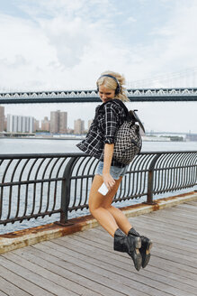 USA, New York City, Brooklyn, happy young woman with headphones and cell phone jumping at the waterfront - BOYF01150