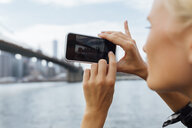 USA, New York City, Brooklyn, young woman at the waterfront taking a cell phone picture of Brooklyn Bridge - BOYF01153