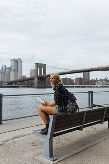 USA, New York City, Brooklyn, smiling young woman sitting at the waterfront with backpack and tablet - BOYF01159