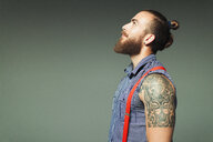 Curious hipster man with beard and shoulder tattoo looking up - CAIF22378