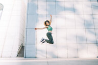 Portrait of happy young woman jumping at a building - OCMF00162