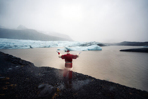 Iceland, rear view of a man disguised as Santa Claus standing at a glacier raising his arms - OCMF00165