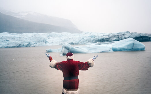 Iceland, rear view of a man disguised as Santa Claus standing at a glacier raising his arms - OCMF00168