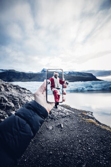 Iceland, man disguised as Santa Claus coming out of a cell phone - OCMF00171