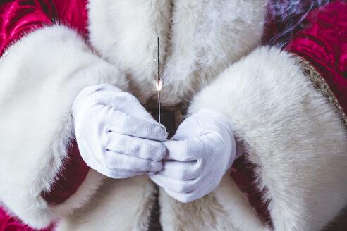 Hands of Santa Claus holding burning sparkler, close-up - JCMF00031