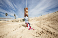 Girl with American flag in barren landscape - ERRF00168