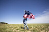 Man holding American flag on field in remote landscape - ERRF00186