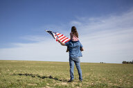 Man with daughter and American flag standing on field in remote landscape - ERRF00189