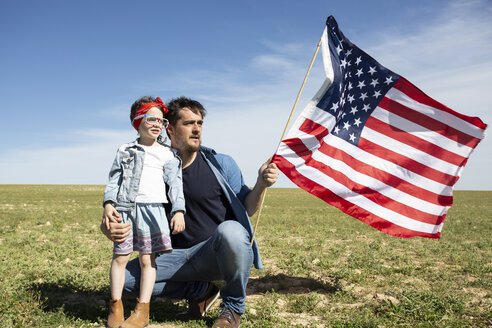 Man with daughter and American flag on field in remote landscape - ERRF00192