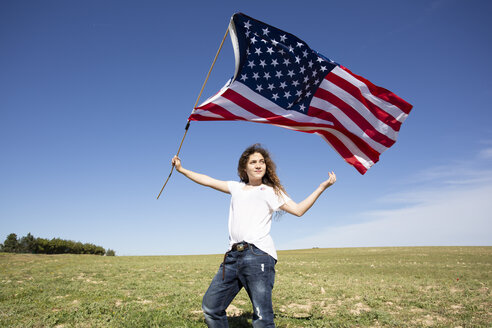 Girl holding American flag on field in remote landscape - ERRF00195