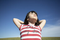 Girl with closed eyes enjoying sunshine in remote landscape - ERRF00198