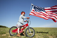 Girl with bicycle and American flag on field in remote landscape - ERRF00201