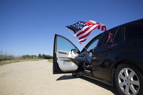 Girl with American flag sitting in car on path in remote landscape - ERRF00207