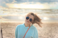 A young woman wearing sunglasses on the beach - INGF08363