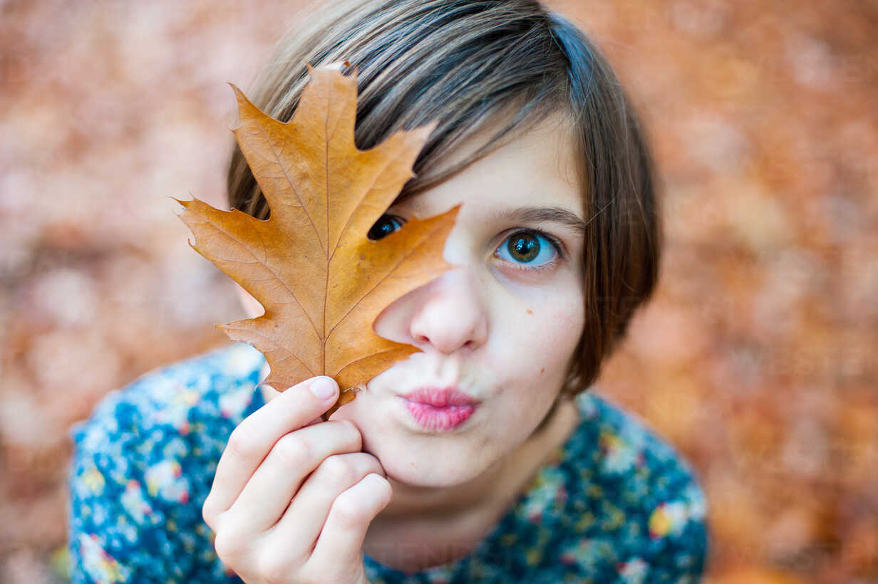 Head shot of a girl holding an autumn leaf - INGF08417 - Ingram Image/Westend61