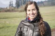 Portrait of smiling female biker wearing leather jacket - CAVF57473