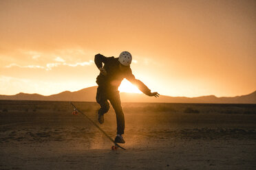 Full length of man performing stunt with skateboard on field against sky during sunset - CAVF57482