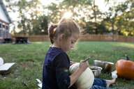 Side view of girl carving pumpkin while sitting in yard during Halloween - CAVF57497