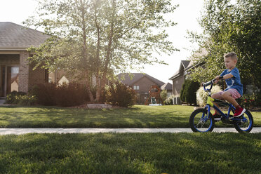 Side view of boy riding bicycle on road amidst grassy field - CAVF57533