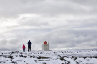 Rear view of father and daughter standing on snow covered landscape against lighthouse and cloudy sky - CAVF57554