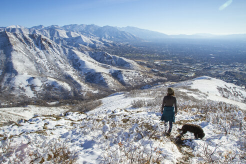 High angle view of woman with dog on mountain during winter - CAVF57563