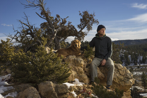 Man with dog sitting on rock formations against sky at Bryce Canyon National Park - CAVF57566