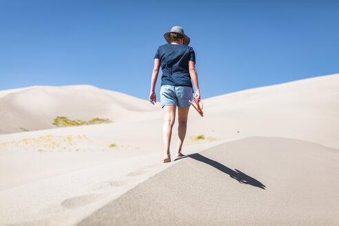 Rear view of woman holding flip-flop while walking on sand at Great Sand Dunes National Park during sunny day - CAVF57569