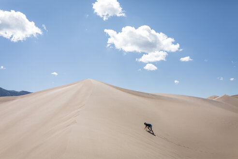 High angle view of woman climbing sand dune at national park during sunny day - CAVF57572
