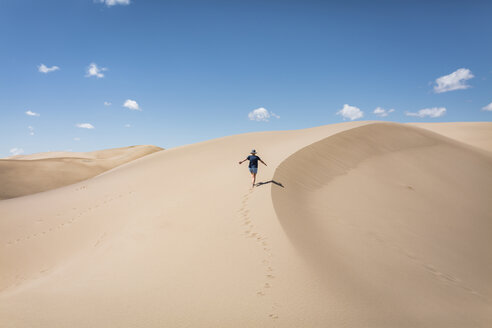 High angle view of carefree woman with arms outstretched walking on sand at Great Sand Dunes National Park during sunny day - CAVF57575