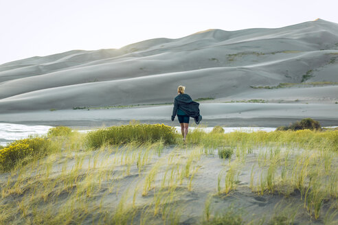 Rear view of woman amidst plants at Great Sand Dunes National Park - CAVF57578