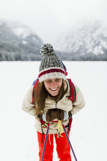 Smiling woman hiking on snow covered field - CAVF57584