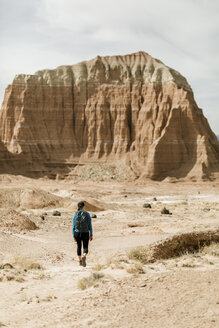 Rear view of female hiker with backpack exploring desert against rock formations during sunny day - CAVF57590