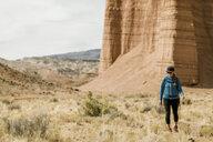 Full length of female hiker hiking at desert against rock formations - CAVF57593