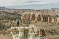 Full length of female hiker standing on rock formation at desert - CAVF57596