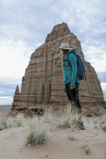 Side view of female hiker standing against rock formations and cloudy sky at desert - CAVF57599