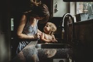 Mother bathing shirtless daughter in kitchen sink at home - CAVF57611