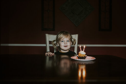 Portrait of cute girl with birthday cake on table at home - CAVF57614