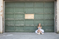 Portrait of ballerina sitting by building - CAVF57617