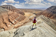 Rear view of athlete with backpack running on mountain trail during race - CAVF57623