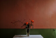 Red flowers in a vase on a table against a red wall - INGF08486