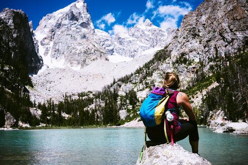 Rear view of female hiker sitting on rock by lake against mountains at Grand Teton National Park - TGBF01788