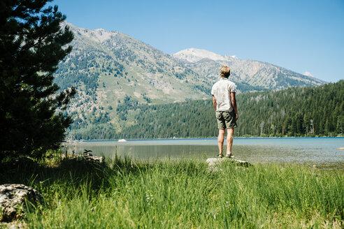 Man standing on rock by lake while admiring mountains at Grand Teton National Park - TGBF01797